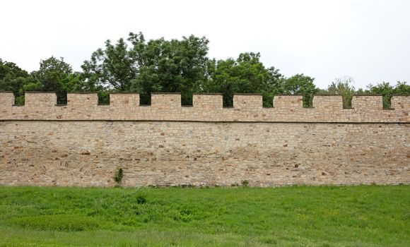 Castle wall with a green lawn in front of it