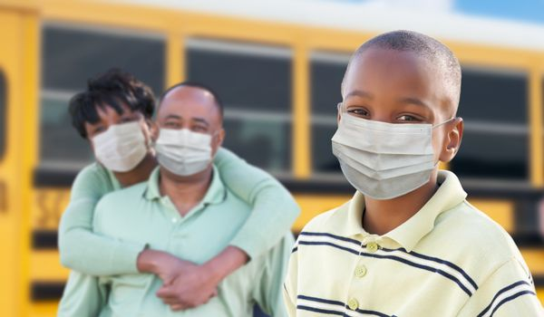 Young African American Student and Parents Near School Bus Wearing Medical Face Masks During Coronavirus Pandemic.