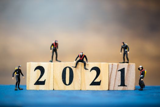 Miniature people divers diving around wooden block 2021 , Happy new Year concept