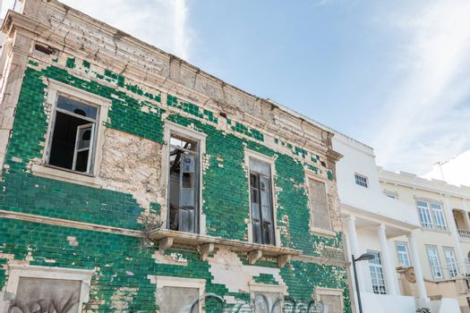 Albufeira, Portugal - May 3, 2018: People looking at a ruined building on the seafront in an upscale part of the resort town on a spring day