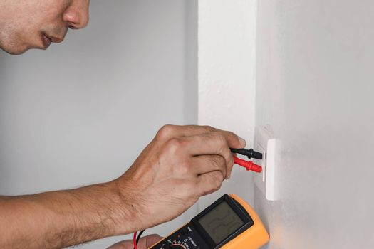 Electrician is using a digital meter to measure the voltage at the power outlet in on the wall.