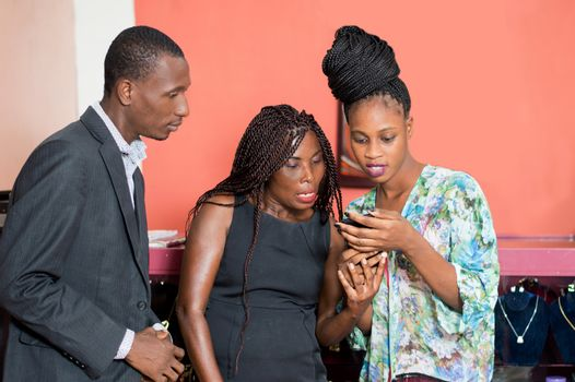Three friends share information on a mobile phone in a jewelry store