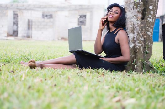 young woman in communication in a park sitting with a laptop on her legs