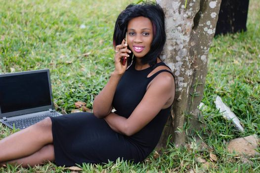 pretty girl in communication next to a tree with her laptop open