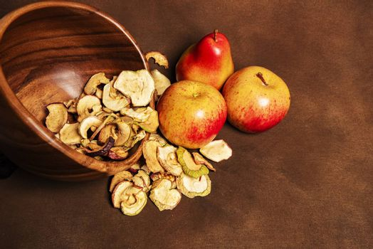 Pile of dried apples together with two whole apples and one pear lying in a wooden bowl. Still life concept of fall season harvest and homemade fruit processing