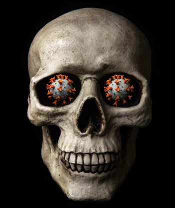 Human skull with coronavirus in place of eyes isolated on a black background. This virus caused global pandemic of COVID-19 disease. Health complication as pneumonia, serious cough and high fever can cause death