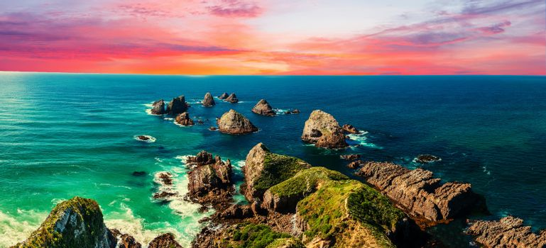 Sunset over Nugget Point which is located in the Catlins area on the Southern Coast of New Zealand. There area many rock islands - nuggets - in the sea. Panoramic photo