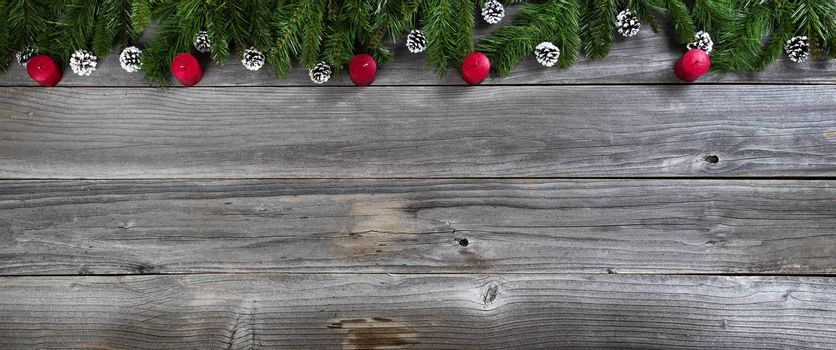 Merry Christmas and Happy New Year concept with red candles inside of fir branches on rustic wooden boards