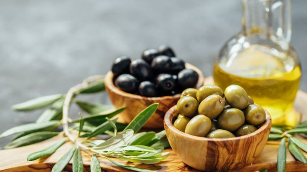Set of green and black olives and olive oil on gray background. Different types of olives in olive wooden bowls and olive oil over wooden cutting board and olive leaves. Copy space. Horizontal banner