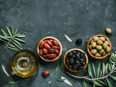 Set of green, black and red or pink olives and olive oil on dark background. Different types of olives in olive wooden bowls and olive oil over dark canvas background. Copy space. Top view or flat lay