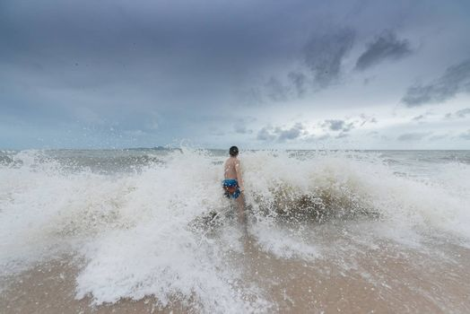 An Asian boy has felt happy and fun on the beach with a cloudy sky.