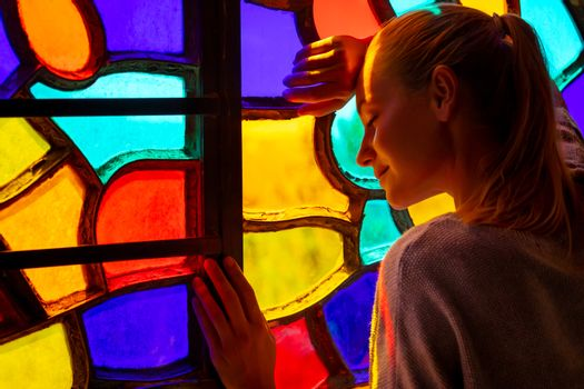 Nice Peaceful Female with Closed Eyes near the Colorful Stained Window Thinking about Future. Praying in the Church. Art and Religion Concept.