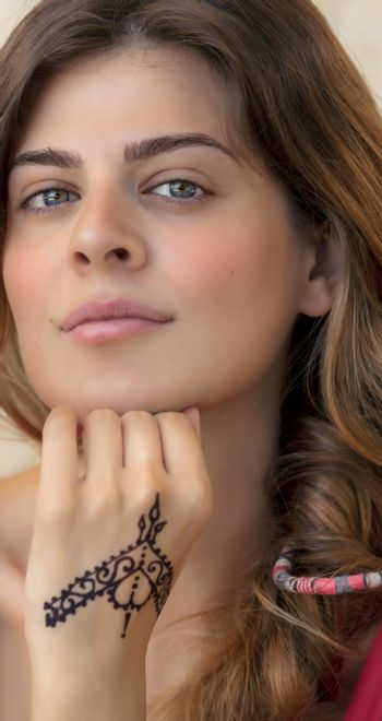 Closeup Portrait of a Nice Female with Beautiful Gentle Mehndi Drawing on her Hand. Stylish Modern Body Painting. Authentic Beauty of Young Caucasian Woman.