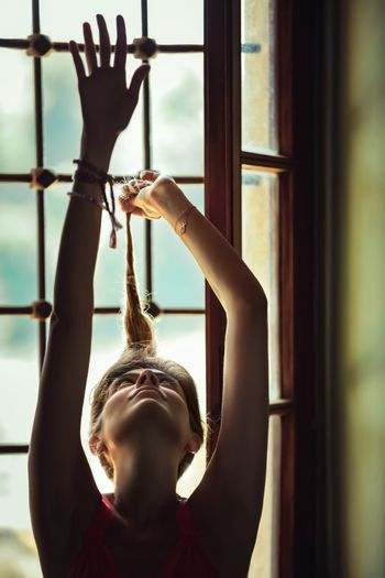 Portrait of a Gorgeous Woman With Raised up Hands near the Window. Gentle Female Dancing at Home.