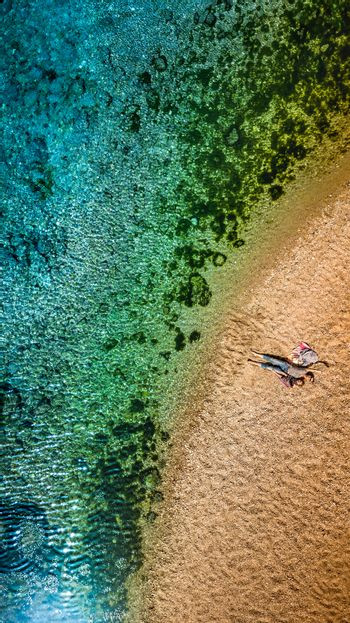 Drone View Photo of a Young Mother and herLittle Son Lying Down on Beautiful Golden Sand on the Tropical Island. Happy Family Enjoying Beach. Vertical Panorama. Flat Lay.