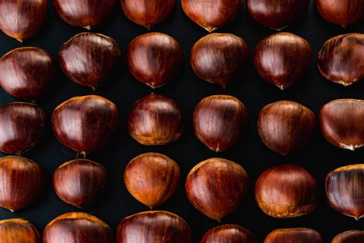 Rows of chestnuts isolated on black background. Chestnuts theme