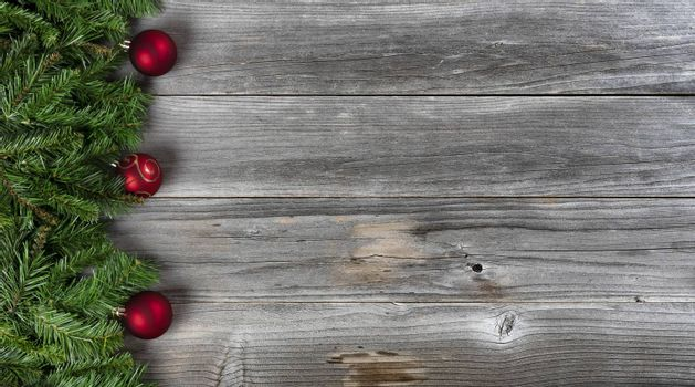 Merry Christmas and Happy New Year concept consisting of fir branches and red ball ornaments on left side of rustic wooden boards