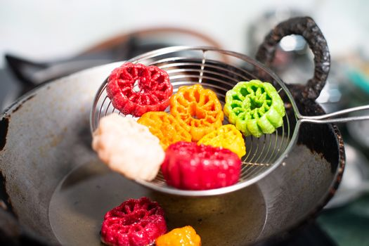 shot of colorful Fryums being shaken to remove excess oil from this popular north indian snack and street food. This sago and potato starch delicacy is a popular snack that is unhealthy but very tasty