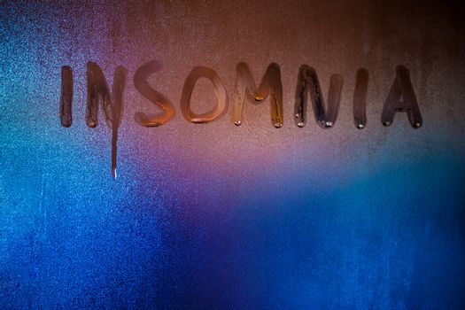 the word insomnia written on night wet window glass close-up with blurred background.