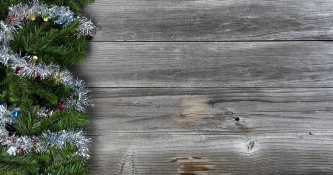 Merry Christmas and Happy New Year holiday concept with silver tinsel on top of fir branches on left side of rustic wood
