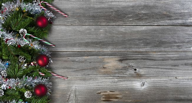 Merry Christmas and Happy New Year holiday concept with silver tinsel and other decorations on rustic wood