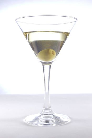 Glass with martini and olive on a white background