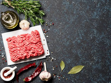 Fresh raw minced beef on backing paper and cutting board and ingredients over dark blue background with copy space. Top view or flat-lay.