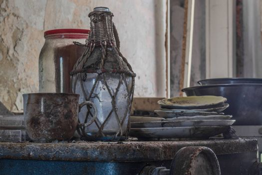 Bottle with dishes on a rusty stove in a house