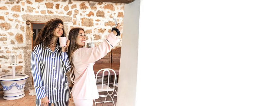 Two beautiful mixed race young women that living together, just wake-up making a self-portrait with smartphone holding a cup of tea outdoor in their country house porch - Big white copy space