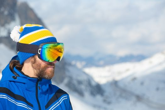Skier in goggles look at mountains