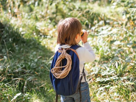 Curious boy is hiking in forest. Outdoor leisure activity for kids. Child looks through binoculars on tree foliage. Sunny day at autumn or summer day.