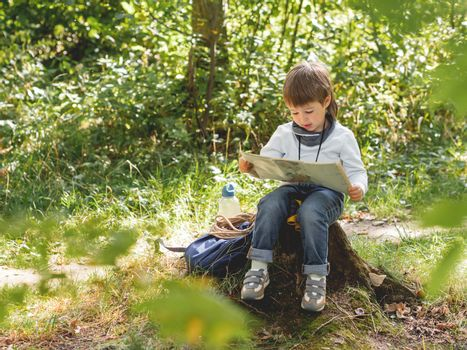 Little explorer on hike in forest. Boy with binoculars, backpack, water bottle and rope sits on stump and reads map. Outdoor leisure activity for children. Summer journey for young tourist.