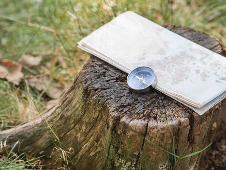 Compass and map lie on stump in forest. Tourist's gear for hiking. Summer adventure. Outdoor recreation. Active lifestyle.