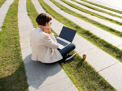 Freelance business woman sits in park with laptop and take away cardboard cup of coffee. Student studies online. Casual clothes, urban lifestyle of millennials.