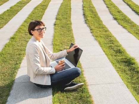 Business woman sits in park with laptop and take away cardboard cup of coffee. Casual clothes, urban lifestyle of millennials.