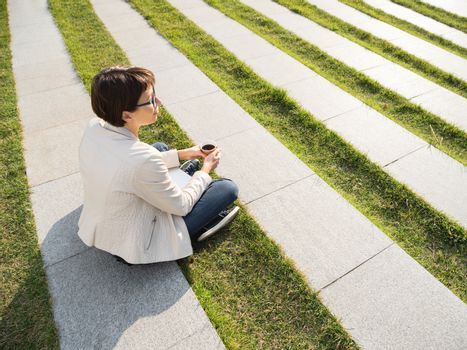 Woman with short haircut and eyeglasses sits in park with take away cup of coffee. Woman enjoys summer sun. Casual clothes, urban lifestyle of millennials.