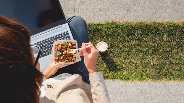 Woman sits on park bench with laptop and take away lunch box, cardboard cup of coffee. Healthy bowl with vegetables. Casual clothes, urban lifestyle of millennials. Healthy nutrition. Copy space.