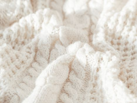 Hand made cable-knit sweater sweater. Texture of warm knitted fabric with pattern. White crumpled cardigan. Cozy autumn outfit for snuggle weather.