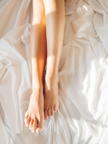 Morning bedtime. Woman's feet on unmade bed. Sunbeams on white crumpled bed sheet. Light and shadow.