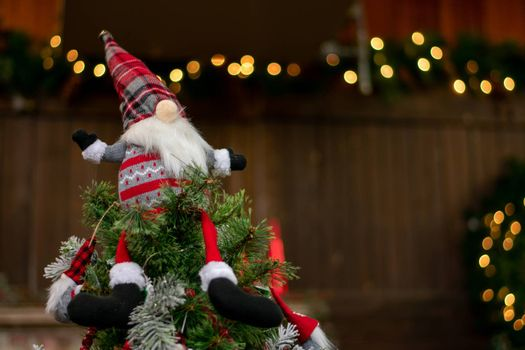A Christmas Gnome Dressed in a Red Sweater and Hat With a Big Nose on Top of a Christmas Tree With Bokeh Christmas Lights in the Background