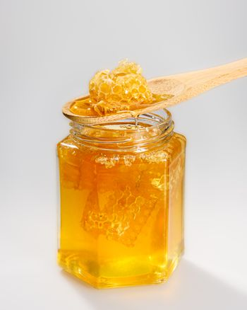 A jar of honey and a spoon with honeycomb