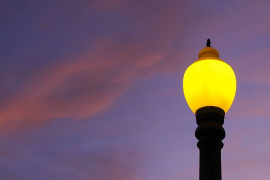 Colorful lamppost illuminating the afternoon. Blue sky and pink clouds in the background.