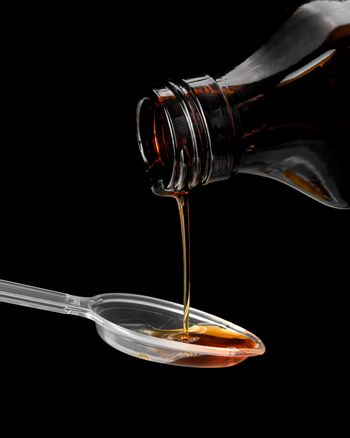 Syrup is poured into a spoon, close - up on a black background