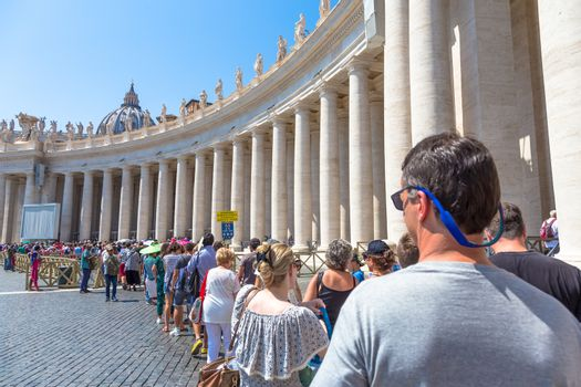 ROME, VATICAN STATE - AUGUST 24, 2018: long line of people waiting in front of Saint Peter Basilica entrance. Concept for overtourism and mass-tourism.