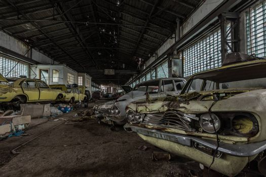 many demolished abandoned cars in a hall