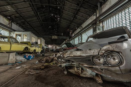 many accident cars in a large hall of a workshop