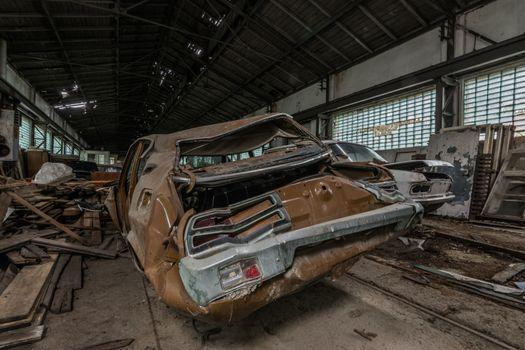 old brown demolished car in an abandoned car workshop
