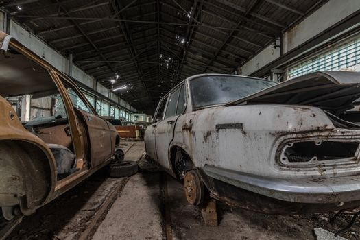old rusty cars in a hall of a car workshop