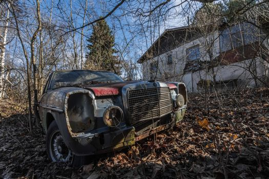 Rusty Mercedes car on an abandoned property with a house