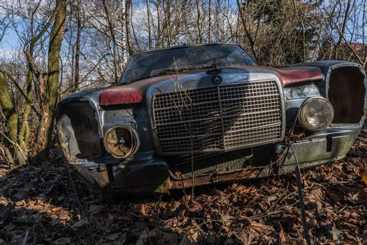 rusty red mercedes on an abandoned property
